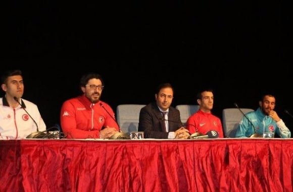 Panelden bir fotoğraf karesi. Ortada rektör yardımcısı, sağ ve solda sporcular bir masada oturmuş durumdalar. Önlerinde mikrofon var